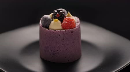 pite : Round mousse dessert with fresh berries rotating on black background