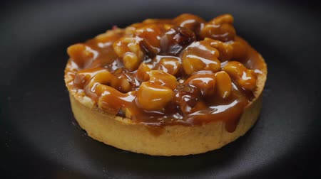 black walnut : Tart with nuts and caramel rotating on black plate