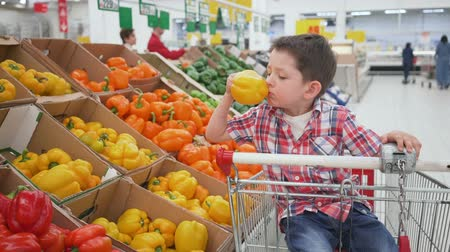 healthyfood : little boy in supermarket smelling yellow bulgarian pepper sitting in the trolley. Shopping in store, fresh products for kitchen and cooking.