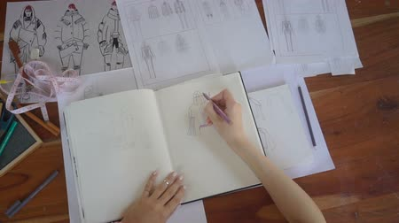 tırnak : Top view of the designer with a pen, designing and sketching new collection