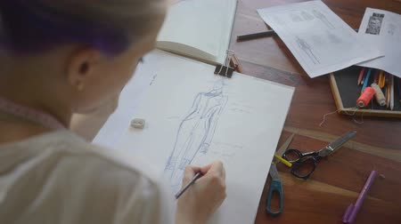 tırnak : Female designer with a pen, designing and sketching new collection. There is creative mess with different stuff on the table.