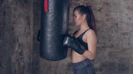 bokser : Young tired woman in boxing gloves standing near the punching bag during workout in gym Stockvideo