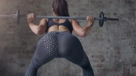 штанга : Back view of girl in black sportswear holding bar making weight-lifting exercise