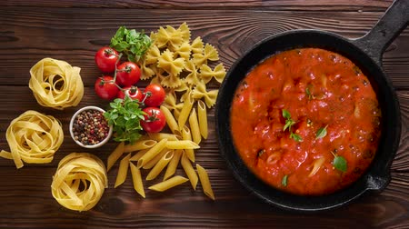 olasz konyha : Cinemagraph loop. Cooking pasta penne with tomato sauce and basil on iron cast pan. Wooden table, top view