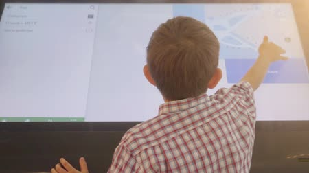 konzol : Child is using a touch screen of interactive information stand