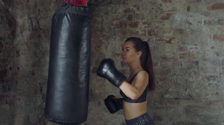 femminismo : Side view of girl in black sportswear training with punching bag on the background of a brick wall Filmati Stock