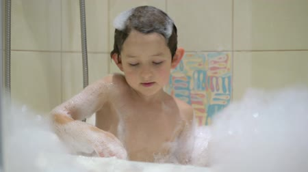 szampon : Funny child playing with water and foam in a bathroom Wideo