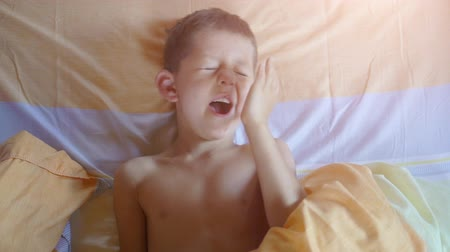 wakes : Top view of a young boy yawning in bed