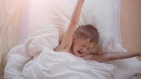 geeuwen : Top view of a young boy yawning and stretching in bed