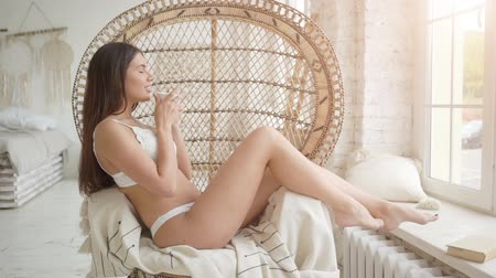 armchairs : Sexy young woman in white lingerie enjoying morning coffee, sitting in cozy armchair in front of window at home Stock Footage