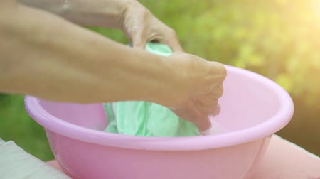 deterjan : Old woman hands washing clothes in a pink plastic basin
