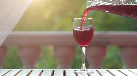 abeceda : Homemade wine pouring into glass on green nature background