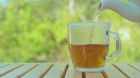 ceramika : Tea pouring into cup from teapot on green nature background Wideo