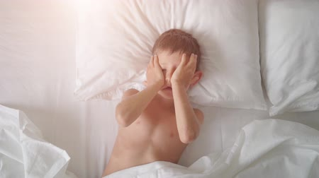acordar : Top view of a young boy yawning and stretching in bed
