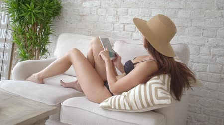kadın iç çamaşırı : Girl in straw hat and black lingerie sitting on couch and shopping online with her tablet pc