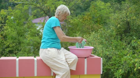 lavanderia : Old woman washing clothes in a pink plastic basin on nature green background Stock Footage