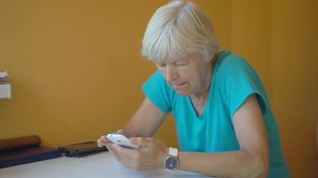 reclináveis : Senior woman using smartphone in living room
