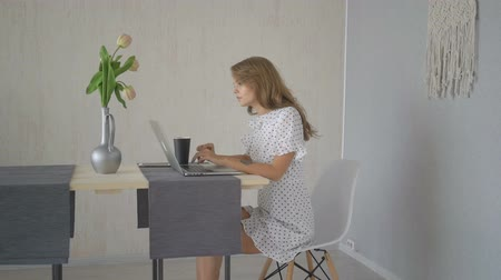 salle de conférence : Cheerful young girl having video chat with friends using laptop at home