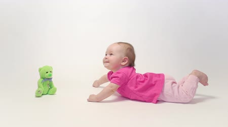 ползком : Adorable baby girl learning to crawl and playing with colorful toy in white background
