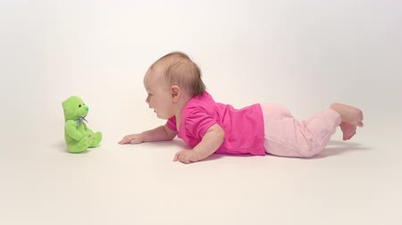 puericultura : Cute baby girl playing with soft toy on white background