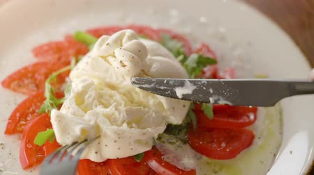 oliwki : Eating delicious burrata cheese with tomatoes cutting with knife and fork
