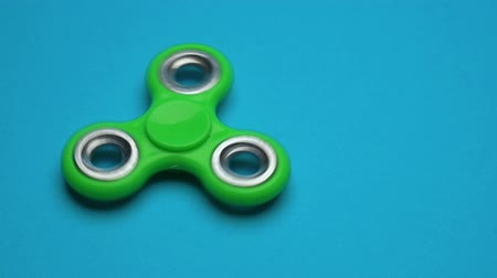 fad : Green fidget spinner on blue background Stock Footage