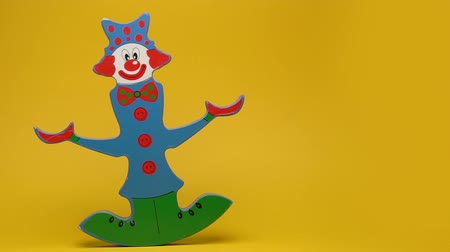 долл : Funny wooden clown on yellow background