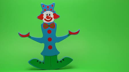 долл : Funny wooden clown on green background