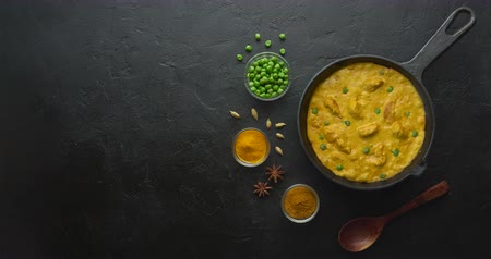çili : Cinemagraph loop. Cooking tasty chicken curry in pan with spices. Flat lay, top view with copy space Stok Video