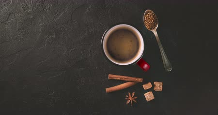 canela : Cinemagrah loop. Coffee mug with cinnamon sticks on dark table. Top view with copy space