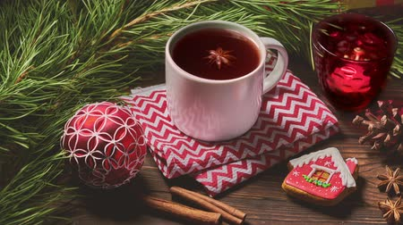 peperkoek : Cup of fruit tea and Christmas decorations on wooden table with fir tree branches Stockvideo