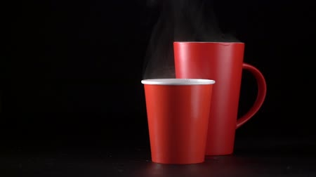 grãos de café : Cinemagrah loop. Steaming red coffee cups on a black background