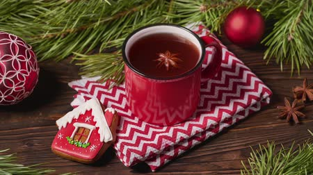 bombki : Red mug of fruit tea and Christmas decorations on wooden table with fir tree branches Wideo