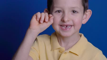 perdão : Litle caucasian boy holds a dropped milk tooth between his fingers