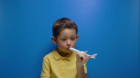 piloot : Happy boy playing with white airplane over blue background Stockvideo