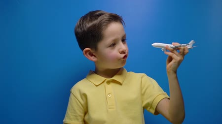 piloot : Happy child playing with toy airplane in hands over blue background Stockvideo