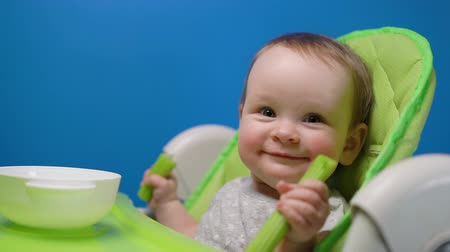 долл : Adorable baby girl eating green fresh celery stick and looking at camera