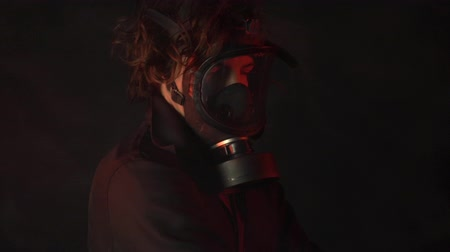 zbourán : Young man in gas mask among poison smoke on dark background. Apocalypse or armageddon concept.