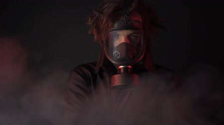 respirator : Young man in gas mask and black clothes among poison smoke on dark background
