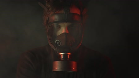 přežití : Young man in gas mask with poison smoke on dark background. Apocalypse or armageddon concept.