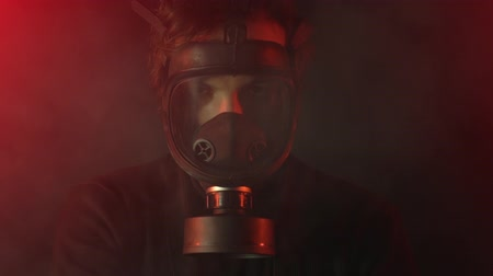 radiation : Environmental disaster. Post apocalyptic survivor in gas mask among poison smoke on dark background