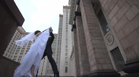 weddings : Bride and groom dancing on the background of the building on the street
