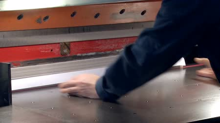 impressão digital : The worker inserts the stack of paper in the machine for cutting uneven edges