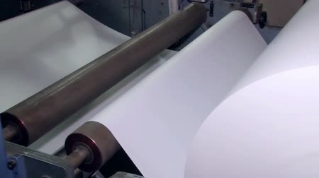 impressão digital : A wide paper roll is rotated on the machine for further cuts Stock Footage