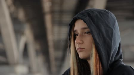 misunderstood : A close up of a teenage girl in a hoody with the hood on and loose multicolored hair spread in the wind under the unfocused bridge pillars scratching a cheek.
