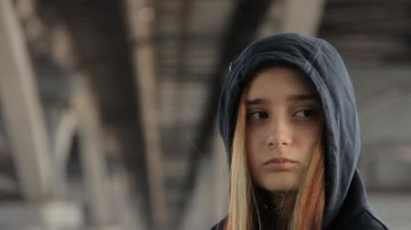 misunderstood : A close up of a teenage girl in a hoody with the hood on and loose multicolored hair spread in the wind under the unfocused bridge pillars watching the car passing by.