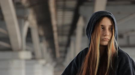 misunderstood : Hipster girl in a hoody with the hood on and loose multicolored hair against the unfocused bridge pillar perspective receding into the distance. Stock Footage