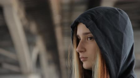 misunderstood : A close up of a teenage girl in a hoody with the hood on and loose multicolored hair spread in the wind under the bridge pillars.