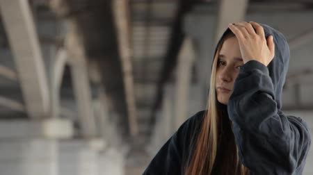 misunderstood : A teenage girl in a hoody with the hood on and loose multicolored hair against the unfocused bridge pillar perspective receding into the distance. Thinking deeply, taking the hood off.
