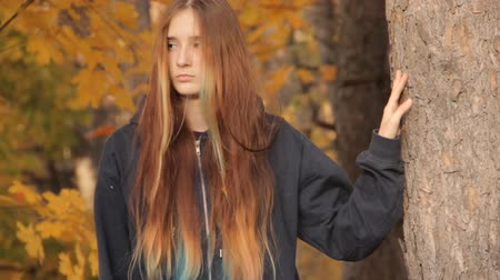açık kahverengi : A girl passing by the camera and moving out of the frame. Loose hair dyed light brown, yellow, green and blue. A yellow maple leaf has fallen on her hair.